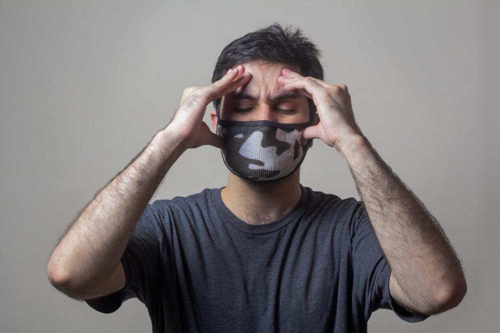 A sick man wearing mask having swear headache. usman yousaf, unsplash